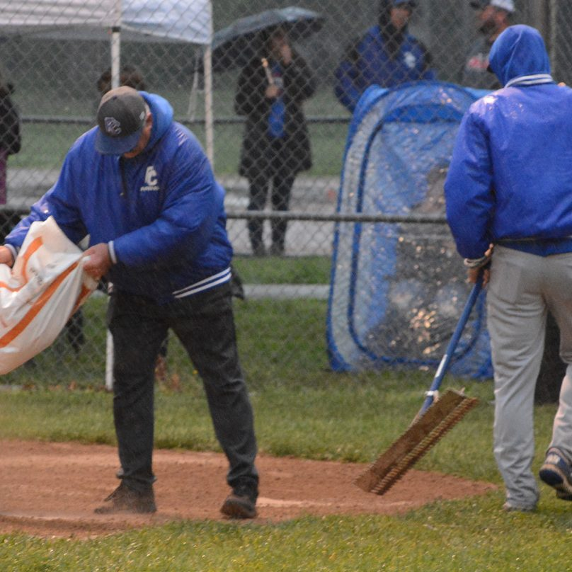 Field crews add field conditioner to the batter's box in an attempt to get the field playable for the district semi-final game that began last Monday night and was suspended in the top of the sixth inning.